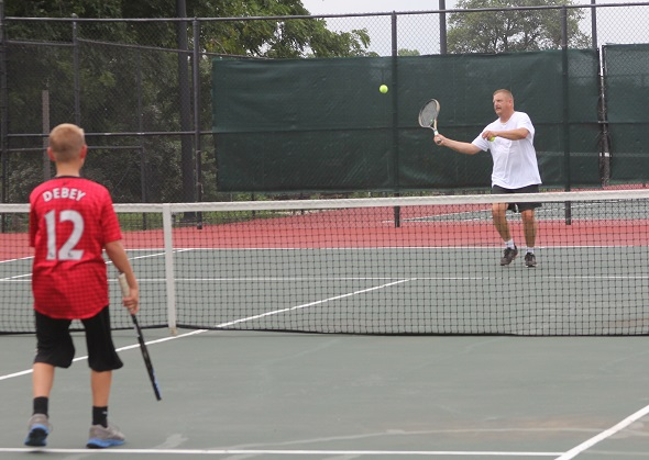 Tyler DeBey and father Rusty playing tennis at Harmon Park.