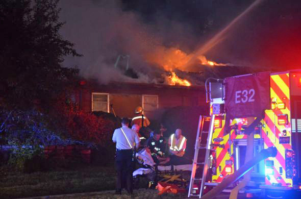 Emergency crews tended to an injured firefighter on a stretcher outside the burning home Tuesday.