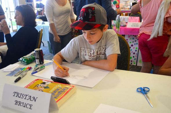 Tristan Bruce was haard at work on a drawing Saturday. The young artist also participated in the timed benefit draw Friday.