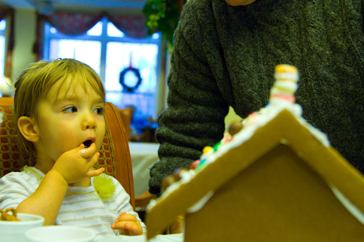 Olive Hays treated herself to a chocolate kiss while decorating her gingerbread house with parents Rob and Robin of Prairie Village.
