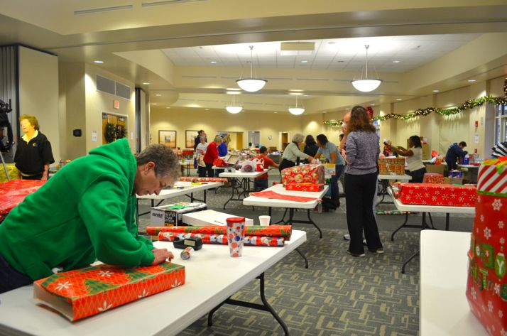 Mary Lohman wraps presents for families Friday morning.