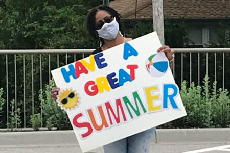 """Ada Wallace holds a """"have a great summer"""" sign"""